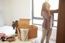 בחורה מתכוננת למעבר דירה עם ארגזים פתוחים