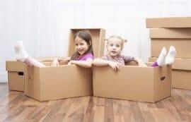 ילדות יושבות בתוך קרטונים המיועדים להובלה