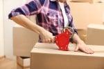 יד של אישה מדביקה ארגז לתכולת דירה