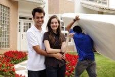 זוג עומד מול בית חדש והמוביל מכניס לבית מזרן